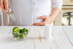 Broccoli di scelta femminili incinti sopra le vitamine Immagini Stock Libere da Diritti