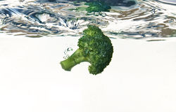 Broccoli die in water valt Stock Foto's