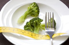 Broccoli on dish with measure tape Stock Photos