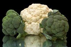 Broccoli en bloemkool op een zwarte Stock Afbeeldingen