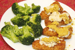 Broccoli and Fish Fillets. Prepared lunch of buttered organic broccoli and cooked breaded pollock fish fillets topped with grated horseradish and deli stone royalty free stock photography