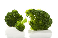 Broccoli florets. Three boiled broccoli florets on white surface Royalty Free Stock Photos