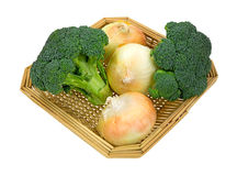 Broccoli Florets Onions In Basket Side. A side view of two broccoli florets and three large sweet onions in a basket on white Royalty Free Stock Image