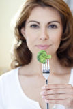 Broccoli on Fork with Girl. Close-up of broccoli on fork with woman in out of focus background Royalty Free Stock Photo