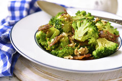 Broccoli with fried bacon and walnuts. royalty free stock photography