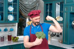 Broccoli gives power to man. bicep or broccoli chose. Guy holds broccoli in hands and shows his bicep. Fresh vegetables for man muscles. Chef loves cooking Royalty Free Stock Images