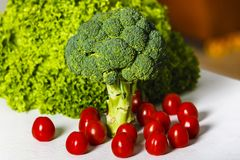 Broccoli, green lettuce and cherry tomatoes. On a table Stock Images