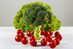 Broccoli, green lettuce and cherry tomatoes. On a table Stock Photography