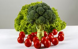 Broccoli, green lettuce and cherry tomatoes. On a table Royalty Free Stock Images