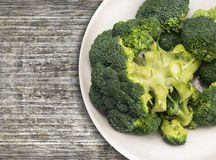 Broccoli head in white bowl on old wooden. Table,clouse up, opy space Royalty Free Stock Photo