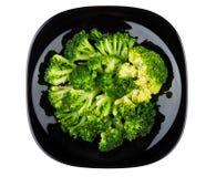 Broccoli i den svarta glass plattan som isoleras på vit Fotografering för Bildbyråer