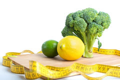 Broccoli, lemon and lime with tape measure. Royalty Free Stock Images