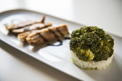Broccoli and mackerel. Mackerel fillets with a splash of balsamic vinegar with broccoli lying on a bed of rice Stock Photos