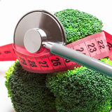 Broccoli with measuring tape and stethoscope . Dieting Royalty Free Stock Photos