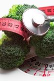 Broccoli with measuring tape on weight scale. Dieting Stock Photo