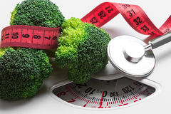 Broccoli with measuring tape on weight scale. Dieting Stock Image