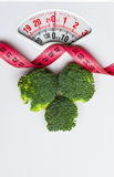 Broccoli with measuring tape on weight scale. Dieting Stock Images
