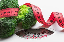 Broccoli with measuring tape on weight scale. Dieting Royalty Free Stock Image
