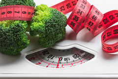 Broccoli with measuring tape on weight scale. Dieting Royalty Free Stock Photos