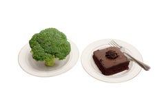 Broccoli och chokladtårtan på vit pläterar Arkivfoton