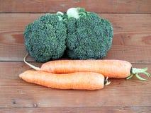 Broccoli och morötter på träbakgrund Royaltyfri Bild