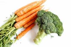 Broccoli och några morötter är på en vit bakgrund ätlig livstid fortfarande royaltyfri bild