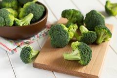 Broccoli op scherpe raad en in de kom op een houten lijst Royalty-vrije Stock Fotografie