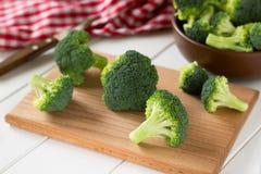 Broccoli op scherpe raad en in een bruine kom worden verspreid die Stock Fotografie