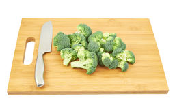 Broccoli pieces over a cutting board. Next to a kitchen knife, isolated over white background Royalty Free Stock Photos