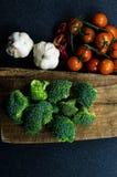 Broccoli, pomodori ed aglio, con il tagliere ed il fondo scuro Fotografia Stock