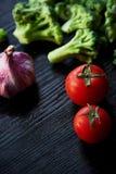 Broccoli, pomodori ed aglio trovantesi su un fondo scuro Cibo sano vegetarianism Vitamine fresche Immagini Stock
