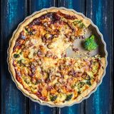 Broccoli quiche. Made in the oven and presented on a blue wooden board royalty free stock photo