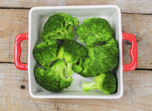Broccoli in red tray. Broccoli in red porcelain tray on wooden table Stock Image