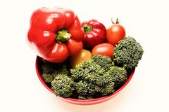 Broccoli, red and yellow tomatoes and bell peppers on plate. Composition of vegetables in red bowl. Set of salad ingredients isolated on white background stock image