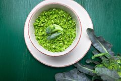 Broccoli rice in bowl on green background. Top view. Overhead. Copy space. Shredded broccoli. Broccoli rice in bowl on green background. Top view. Overhead Royalty Free Stock Photo