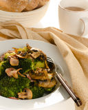 Broccoli sauteed with bacon and mushrooms served on a white plat Stock Image