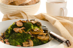 Broccoli sauteed with bacon and mushrooms served on a white plat Stock Photos
