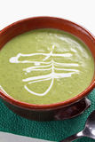 Broccoli Soup. In brown bowl on green napkin with a spoon Royalty Free Stock Photography