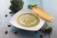 Broccoli soup with heavy cream and sliced almonds. Served with garlic bread baguette Royalty Free Stock Photography