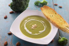 Broccoli soup with heavy cream and sliced almonds. Served with garlic bread baguette Royalty Free Stock Photos