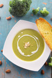 Broccoli soup with heavy cream and sliced almonds. Served with garlic bread baguette Royalty Free Stock Photo