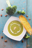 Broccoli soup with heavy cream and sliced almonds. Served with garlic bread baguette Stock Image