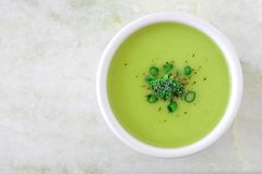 Broccoli soup in white bowl, overhead view on white granite Stock Photos
