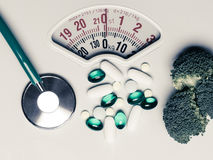 Broccoli stethoscope pills on weight scale. Dieting Stock Image