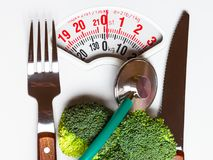 Broccoli with stethoscope on weight scale. Dieting Stock Photo