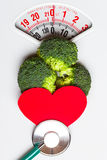 Broccoli with stethoscope on weight scale. Dieting Stock Images