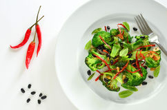 Broccoli stir fry with black beans and thai red peppers. On white plate Stock Photo