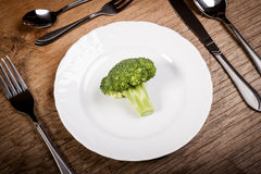 Broccoli su un piatto con la coltelleria su una vecchia tavola di legno Fotografia Stock Libera da Diritti