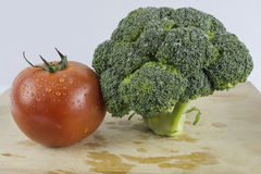 Broccoli and tomato. A broccoli and tomato on a chop board with a white back ground Stock Image