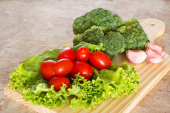 Broccoli, tomatoes, salad and garlic on wooden board. Fresh broccoli, cherry tomatoes and garlic on wooden board on table Stock Photo